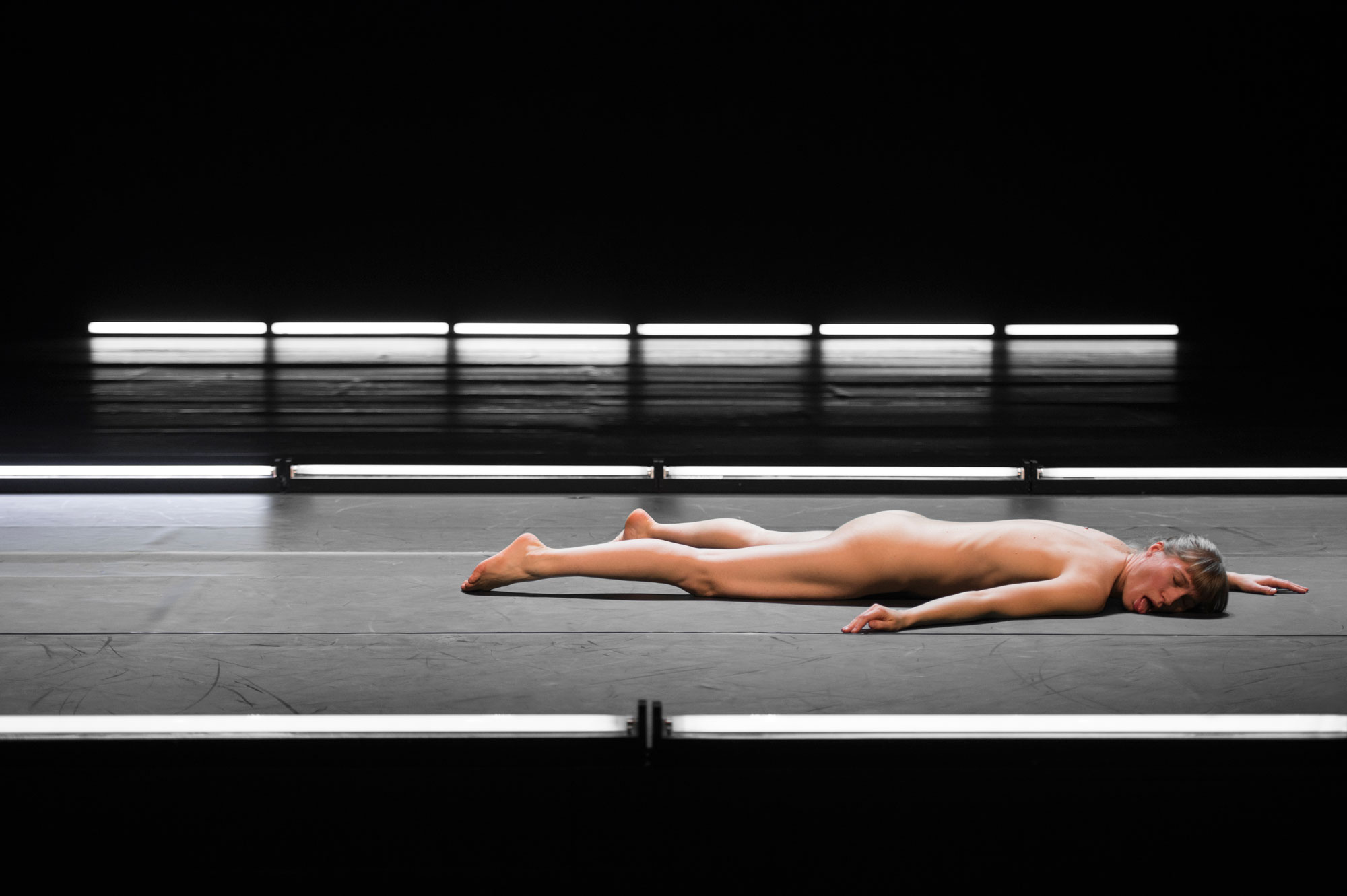 Photo of Mette Ingvartsen lying on stage in 21 Pornographies