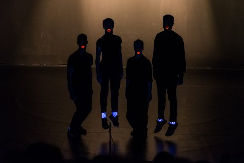 Perfomers in Sofia Mavragani's Afterwords, showing illuminated mouths