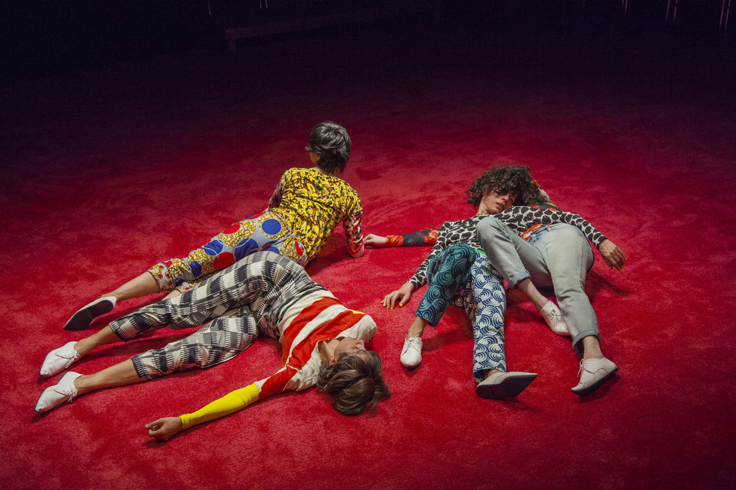 Maria Hassabi, Staged. Performers in coloured costumes on red carpet