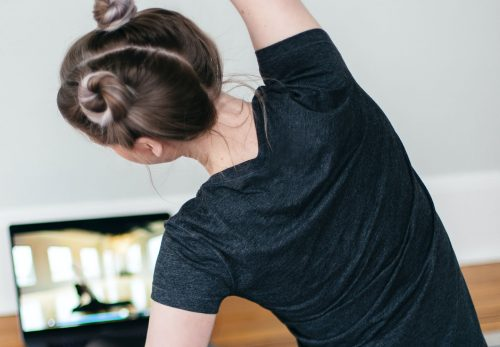 young woman doing exercise with laptop