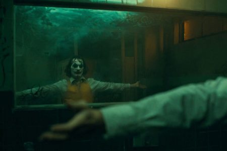Joaquin Phoenix looks in mirror in the bathroom dance scene of Todd Phillips' 2019 film Joker