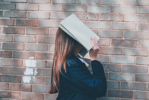 Young woman book covering face