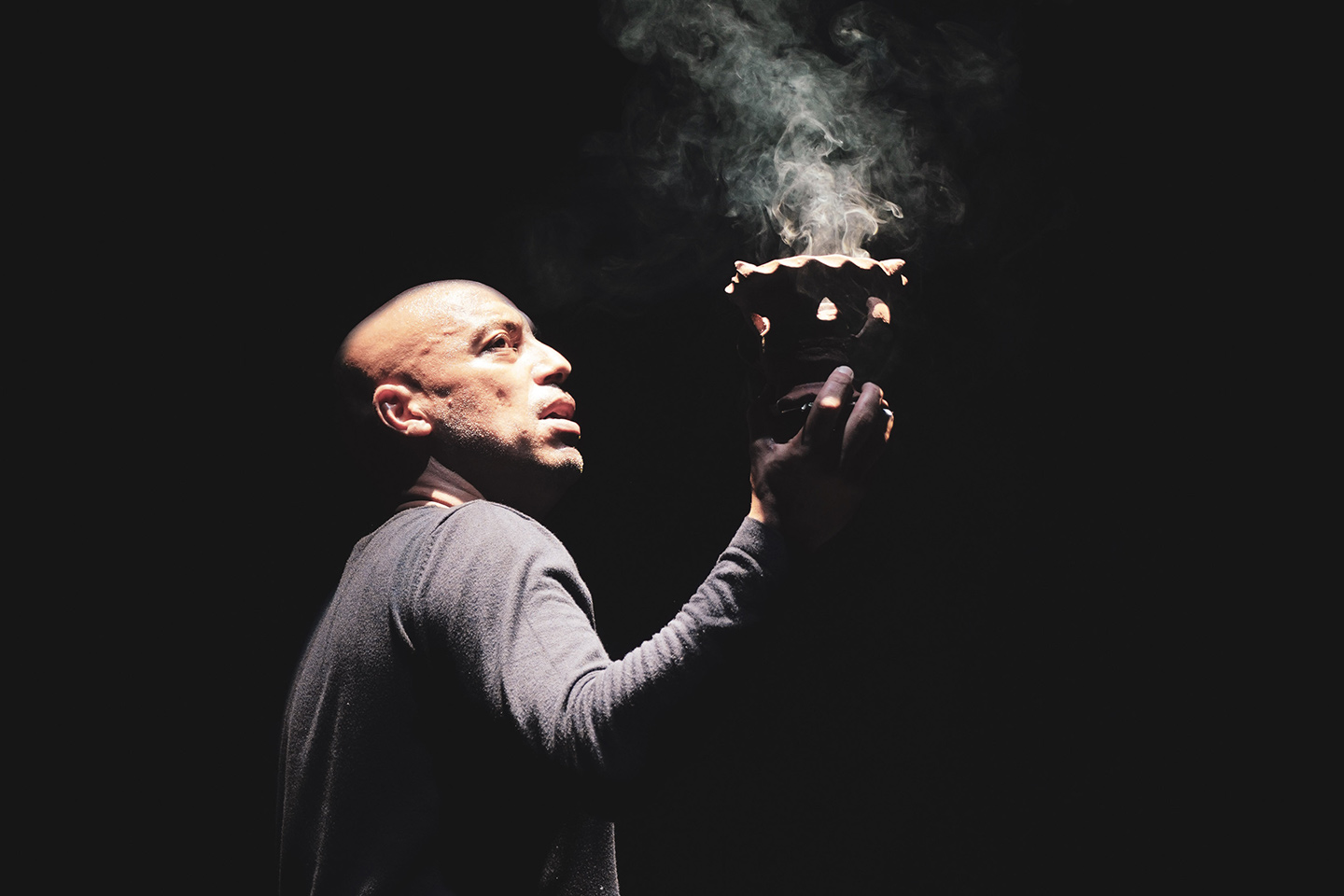 Man (Hamid Ben Mahi) holding a clay lantern with smoke arising from it
