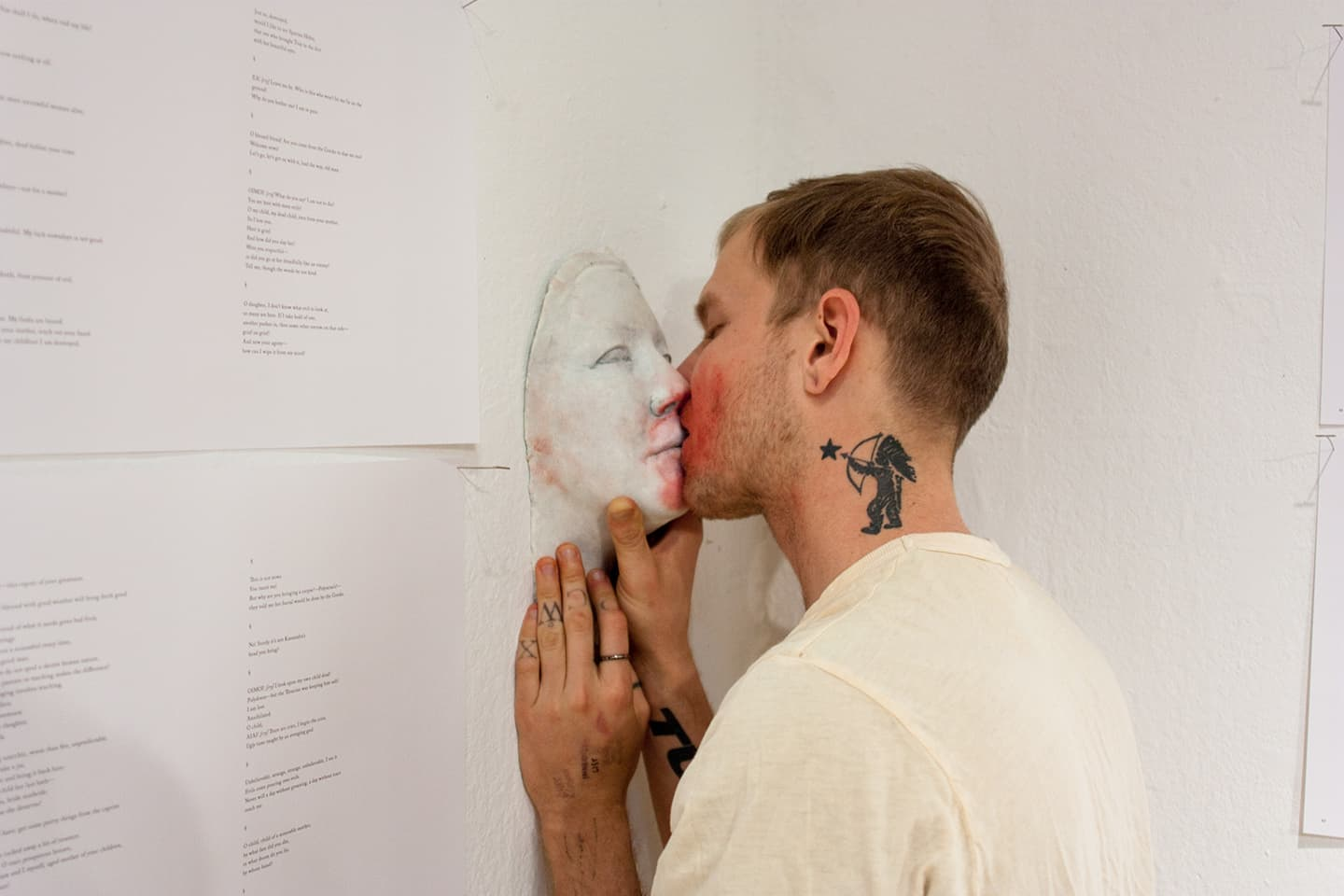 A photograph of a blond man with a shaved head holding a plaster sculpture of Johanna Hedva's face against a wall and kissing it. His eyes are closed. On his neck is a tattoo of a Native American archer pointing an arrow at a star. His fingers and wrists are tattooed with letters and wavering lines, and he wears a ring on his left index finger. Pinned to the white wall around him are pages from the script of Motherload