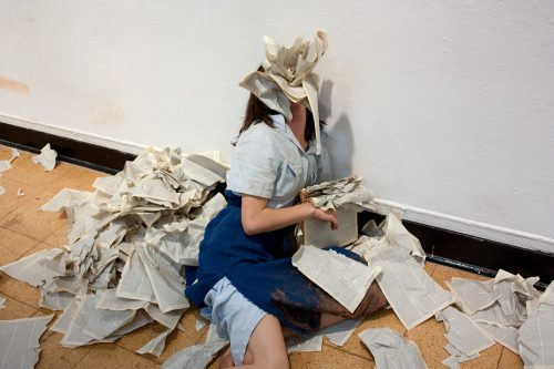 A photograph of a person surrounded by loose pages that they have torn from a book with their mouth. They are leaning against a wall, seated on the floor. Their face is entirely obscured by a mouthful of pages. They have shoulder-length brown hair and wear an apron covered in mud.