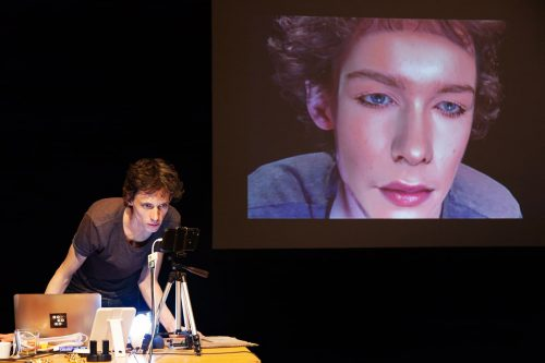 Simon Senn with laptop, microphone and audiovisual equipment at desk. Face of woman, digitally superimposed, on large screen behind him, in the performance Be Arielle F