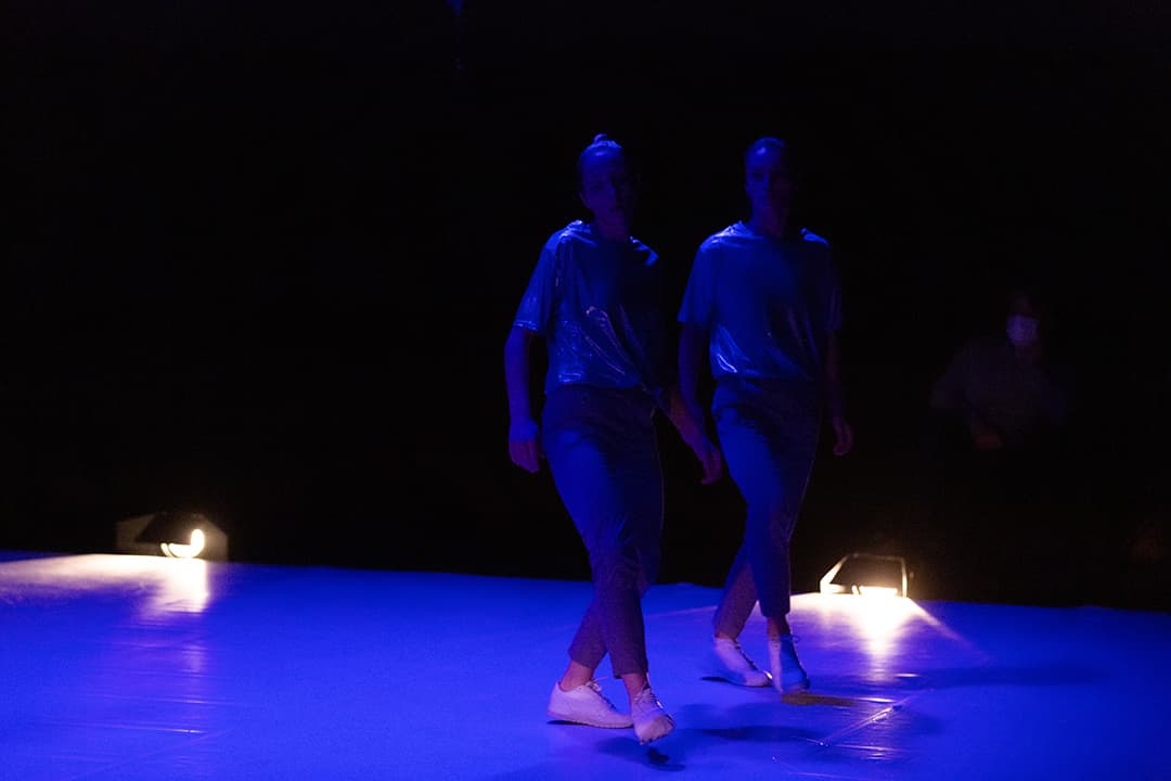 Marion Darova and Martina Apostolova, two women in white sneakers and dark blueish trousers and tops, on a dark bluish stage, with two floor lights behind them, in their stage duet WO MAN