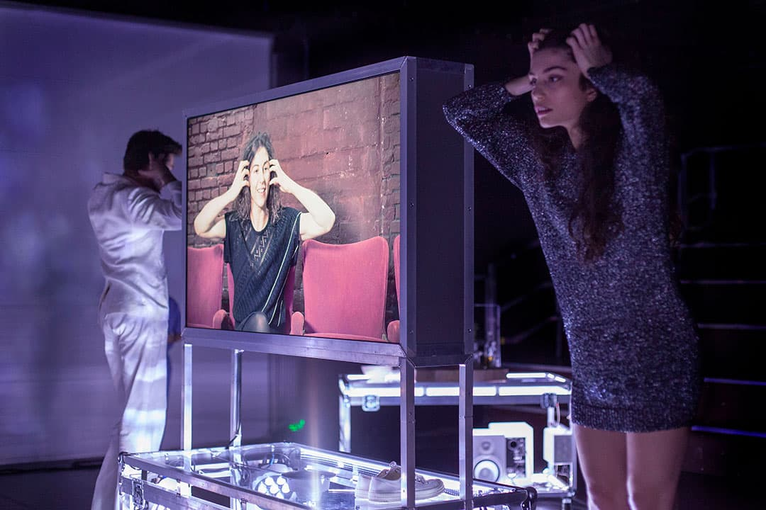 Two dancers on either side of a video screen place their hands to their ears, as does a third woman on the video screen. A moment in Ann Van den Broek's video performance Creating Joy, for her company WArd/waRD
