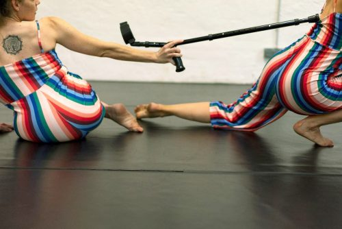 [image description: Katharina and Tanja are wearing the same stripy jumpsuit in colours of blues, green, reds and salmon with bare-skinned arms, shoulders and backs. Tanja is sitting on the floor with her back facing us. She has a round tattoo in the centre of her upper back. Tanja is slightly leaning to the left, which lets parts of her upper body escape the picture frame. Her head is turned to the right and her gaze is following a black crutch, which she is supporting with her stretched-out right hand. The tip of the crutch catchesKatharina's jumpsuit, furling it and revealing more of her white skin. Katharina's two legs and her backside are visible and in a motion of moving towards the right, therefore the rest of her body is escaping the frame. It might even seem as if the crutch is luring Katharina back into the picture? End of description.]