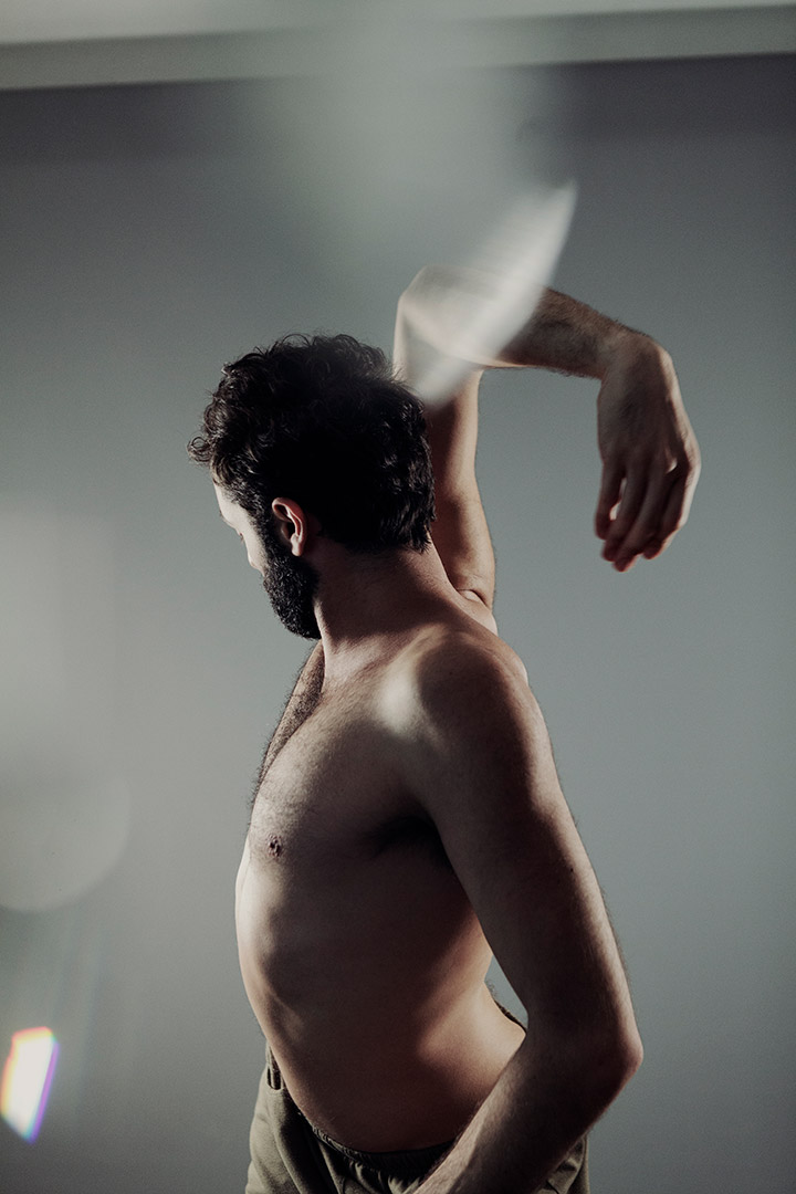 Dancer Charlie Prince with bare torso, facing away, one arm twisted behind head in Cosmic A*