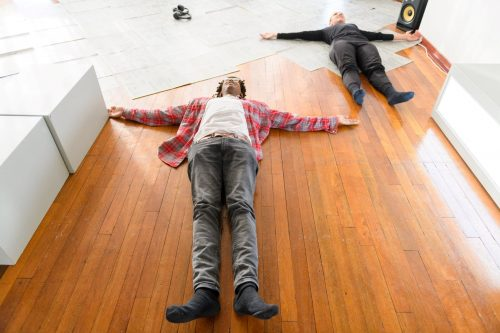A man and a dancer lie spreadeagled on the floor in the same position, in Katja Heitmann's Motus Mori
