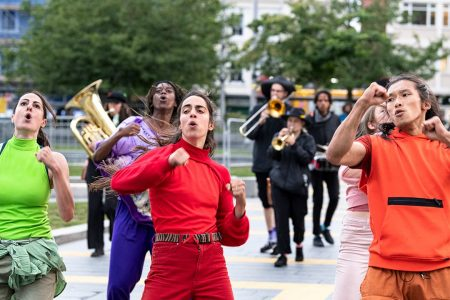 Dancers in bright green, orange, red and purple outfits, in front of a brass band in city square in Woolwich Southeast London. Part of Protein Dance's guided performance En Route.