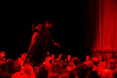 Dark red and black photo of the dance project by PRICE called Melodies are so far my best friend – showing a cloaked man standing on a raised table, surrounded by audience members in Covid facemasks