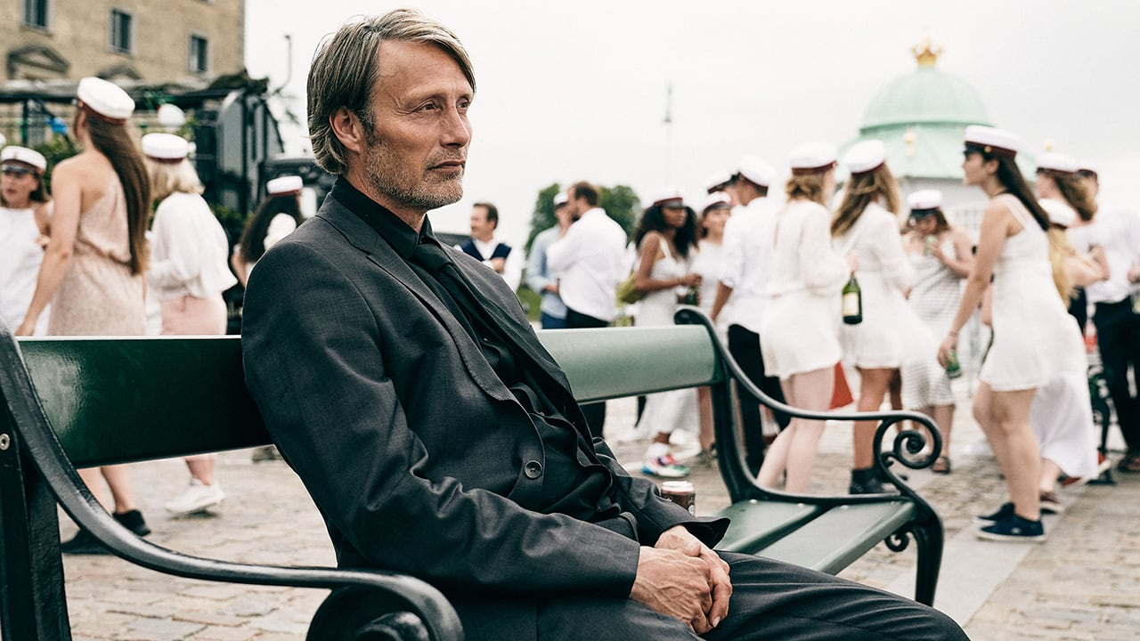 Mads Mikkelsen sits along on a bench as students party behind him in the final scene of Thomas Vinterberg's film Another Round
