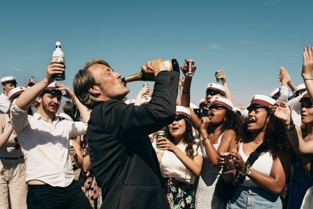 Mads Mikkelsen as Martin, drinking from a bottle surrounded by partying students in the final scene of Thomas Vinterberg's film Another Round